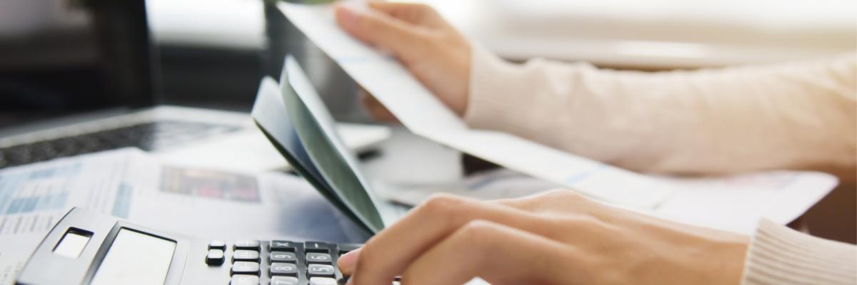 Accountant working through multiple bills using a calculator